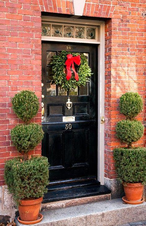 black front door: The Doors, Black Doors, Black Front Doors, Traditional Home, Christmas Doors Decor, Boxwood Wreaths, Christmas Decor, Front Porches, Red Bows