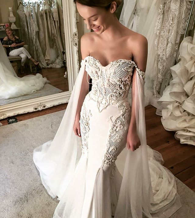 Take a look at this stunning dress from @leahdagloria! The dreamy off-the-shoulder cape, the meticulous laser cut detailing, and the opulent beads and embellishment are things that we love the most from this piece, providing a glamorous and elegant feel but with a unique twist. Who's inspired? Tag a friend who would want this for their big day!