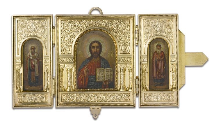 A Russian Gilded Silver Presentation Triptych Icon, Ovchinnikov, Moscow, 1899-1908 | the arched apertures with panels depicting Christ Pantocrator, flanked by St. Nicholas the Wonderworker and St. Vladimir, the frames finely cast and chased with columns and scrolling floral strapwork, the exterior of the hinged doors similarly decorated and closing with a Byzantine cross and shaped hasp