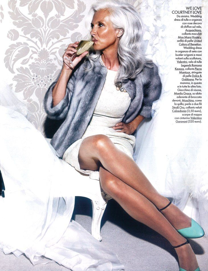 tanned skin, platinum hair, white and gray clothing. stunning.