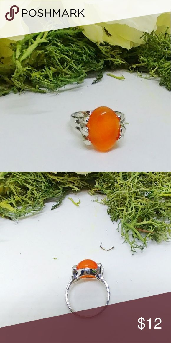 Brand new! Orange Stone Ring Brand new in pkg. Orange polished stone and stainless steel ring Size 7 Really pretty Jewelry Rings