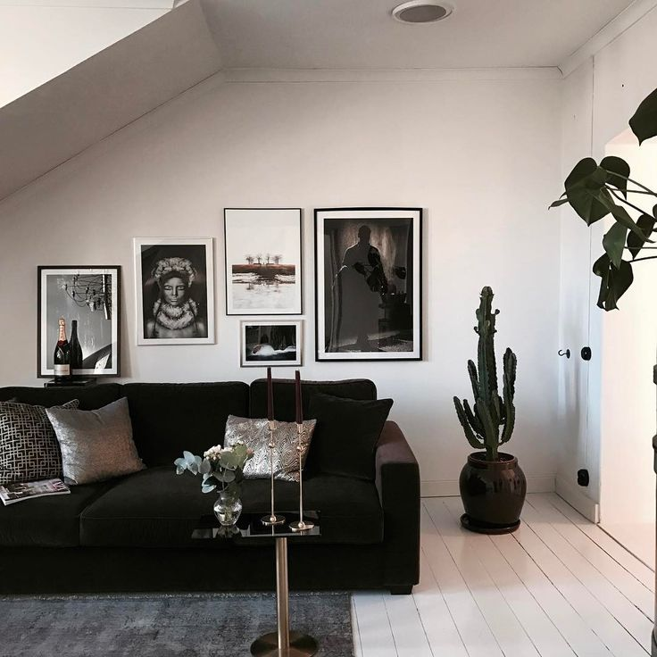 Gorgeous white flat with wooden floors painted white, a cactus and wonderful photowall with framed posters from printler.com, the marketplace for photo art. Interior design by Ariana Heinrici.