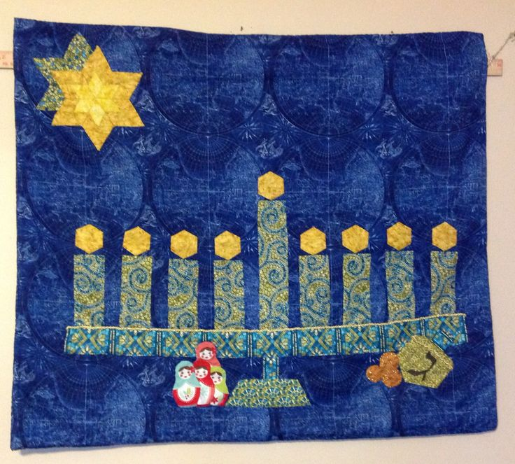 """Happy Hanukkah, the Hanukkah quilt I made. It's call """"Bound by Past, Present, & Future""""  My husband and I were out of town and we went to a fabric store. Robb found the background fabric about 6 years ago. It is a nautical night sky, like a map sailors/mariner would use. It reminded me of traveling to distanced places, long journeys.  The menorah is what looks like shattered stain glass. I thought  of """"kristallnacht"""". In November of 1938 when the German Reich smashed all the Synagogs stained…"""