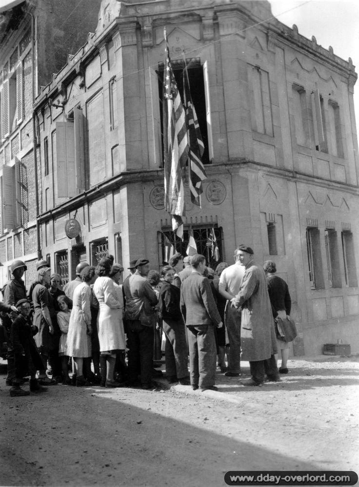 Rue Octave Mirbeau, l'office notarial de Trévières, etude de Maître Charles Pommier, notaire et maire de Trévières, est décorée des drapeaux français et alliés pour 'Independece Day', 4 juillet 1944.