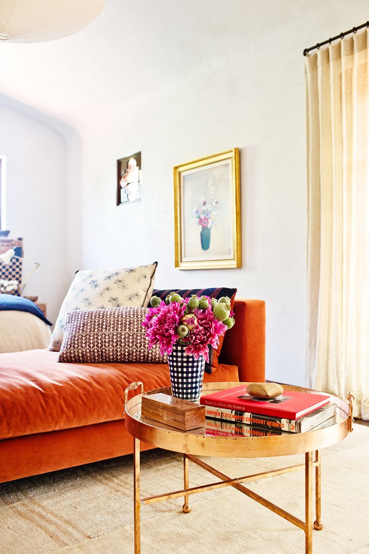 Orange daybed with patterned pillows in bedroom with floral arrangement