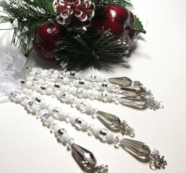 Vánoční ozdoba - rampouch Vánoční ozdona. délka 12 cm. Broušené korálky , bílékorálky,broušená perlička ve tvaru slzy. Zakončeno postříbřenou vločkou. K zavěšení na stromeček , větvičku.Bílá stužka.