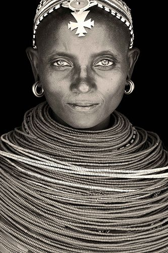 Beautiful African woman from Kenya with gold hoop earrings. She is smiling with her eyes and has a multitude of beaded necklaces around her neck. She has a beaded head piece with a hanging metal cross on her forehead. The picture is black and white with a brown tint.