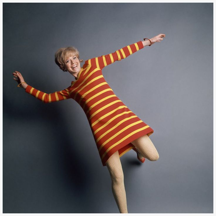 Actress Susannah York wears a red and yellow striped trapeze dress by Deanna Littell for Mam'selle Boutique with textured tights and red shoes, 1967
