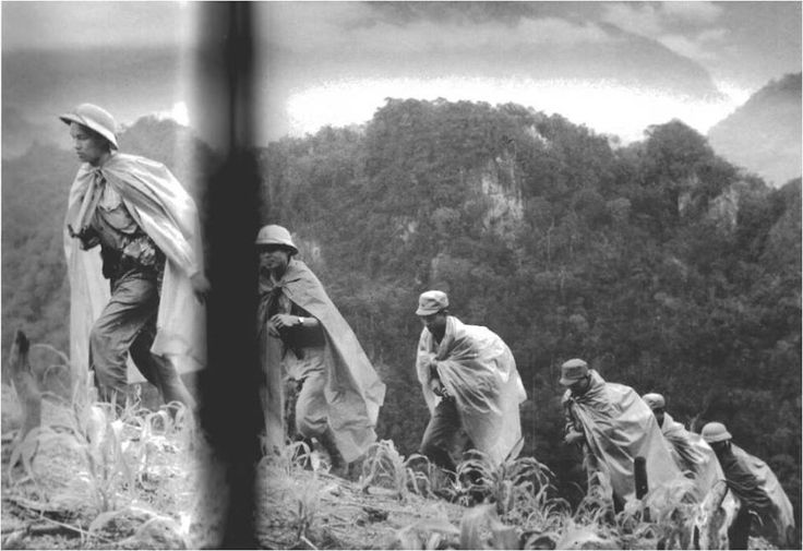 North Vietnamese Army soldiers using plastic sheets as rain capes. They are most likely in North Vietnam, as it was very rare to see the NVA caps pictured in the South.