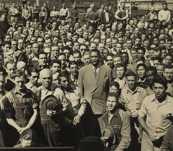 Photograph of Paul Robeson (1898 - 1976) Leading Moore Shipyard Workers in Singing the Star Spangled Banner, September 1942.  Photo credit: National Archives — in Oakland, California.