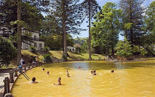 The thermal pool in Furnas, on the island of Sao Miguel, is muddy brown because of iron in the water, with a backdrop of palms, ferns and conifers | via @Telegraph #azores #portugal