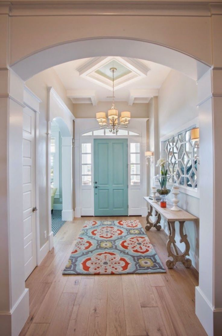 coastal style entry with turquoise front door, white walls, patterned rug