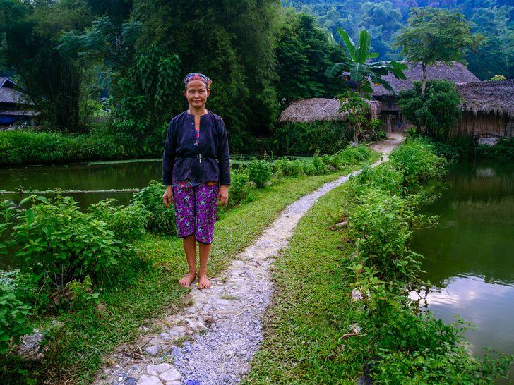 Uma senhora em frente de sua casa na região montanhosa do norte do Vietnã.