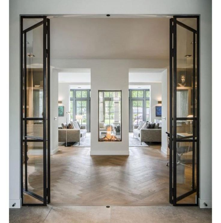 So so pretty!! Neutral living room with herringbone oak floors, steel-frame doors, and incredible modern fireplace.