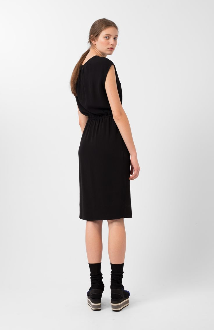 Kinta navy dress. Black crepe dress. Round neckline with pleats on the back. Invisible zip closure on the back. Rubberised natural waist. Approximately knee-length and loose fit.