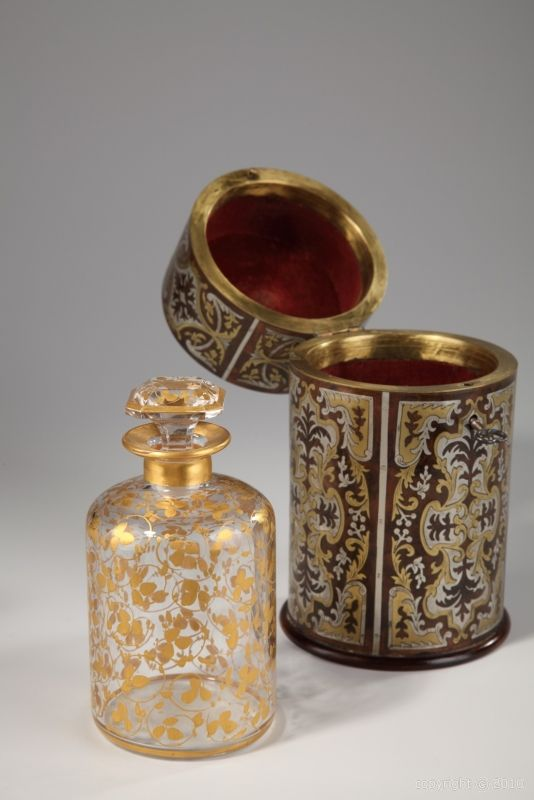 18th century perfume box in wood with brass decoration. 2,200€ Available ITEM AVAILABLE A circular perfume box with its key in the taste of André Charles Boulle richly décorated with flowery rinceau, palmettes and foliages in gilded and silvered brass on dark wood...