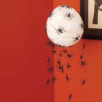 DIY party decoration - cheese cloth over a balloon, plastic spiders on thread.