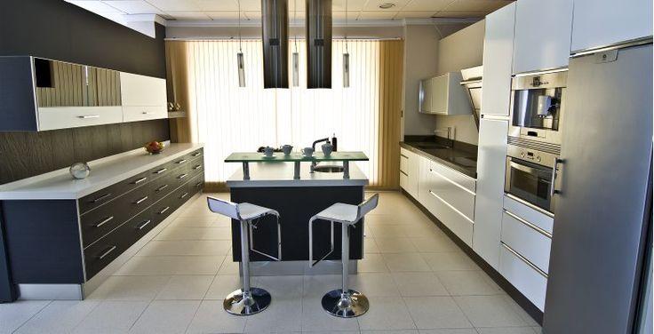 Cocina compuesta por frente de puertas  postformadas  con textura roble en color roble gris, Silestone Tigris Sand más isla de puertas postformadas de color roble gris correderas de cristal Lacobel negro