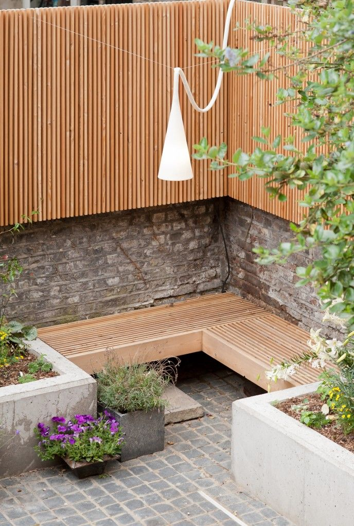Garden Seating Area - the split wood panelling for fence and seating is a wonderful way to coordinate & appreciate the beauty of wodd itself.