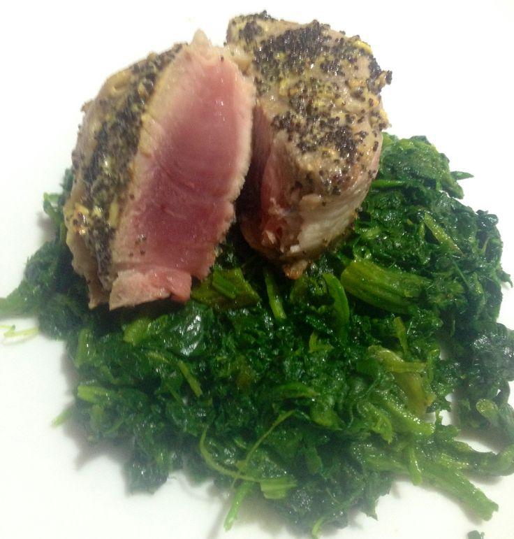 Filetto di maiale alla senape e semi di papavero su letto di spinaci saltati