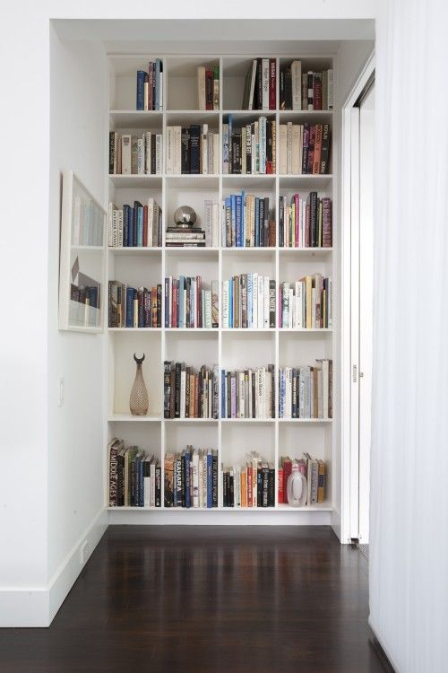 Built in bookcase neat idea.... end a hallway prematurely with an installed bookshelf (don't love these squares, but whatever) and then add molding along the floor to make it 'build in""