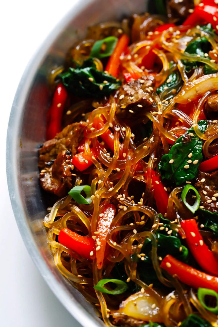 Japchae, this easy Korean noodle stir-fry recipe, is quick and easy to make, it's full of veggies (red peppers, carrots, onions, mushrooms, spinach), and tossed in the most delicious sesame-soy-maple sauce.