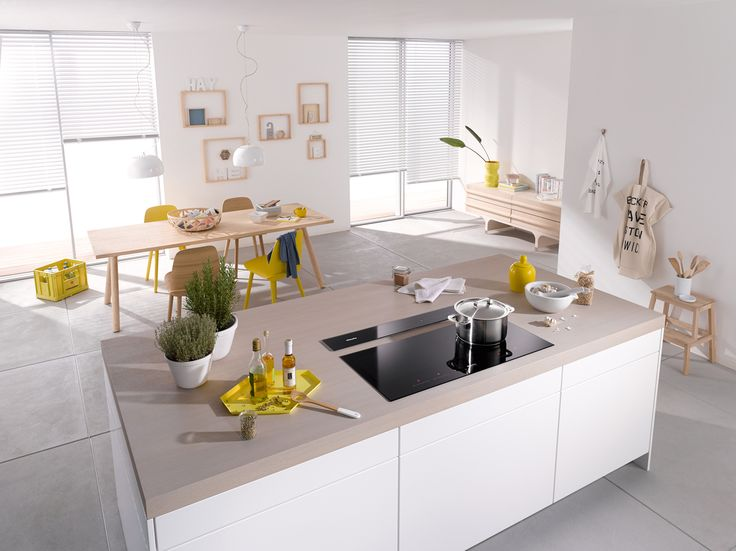 This contemporary open plan kitchen dining space has a central kitchen island featuring a Miele Induction Hob, perfectly placed for entertaining guests whilst cooking #kitcheninspiration