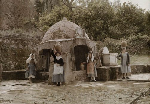 Autochrome: Wilhelm Tobien. Greek women stand outside a stone covered well with water jars. Gastouri, Corfu Island, Ionian Islands, Greece.