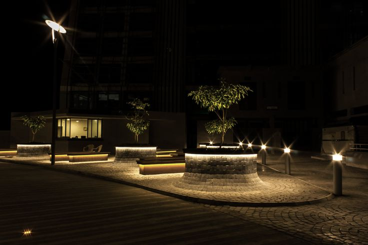 The view of the forecourt to the building complex shows an exciting composition of light and shadow. This is generated by placing lighting under the benches, applying linear light to underscore the planters, and radial lines to mark the steps.