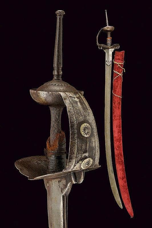 Indian khanda sword, late 18th Century, Strong, curved, single-and false-edged blade, in damask, with double fuller (small defects and some pitting). Iron hilt, with two plates holding the blade through the rivets and are extended forming the quillons. Large guard, ribbed and engraved. Grip with remains of an old covering. Dome-shaped pommel with stalk. Wooden and velvet scabbard of recent production. length 111,5 cm
