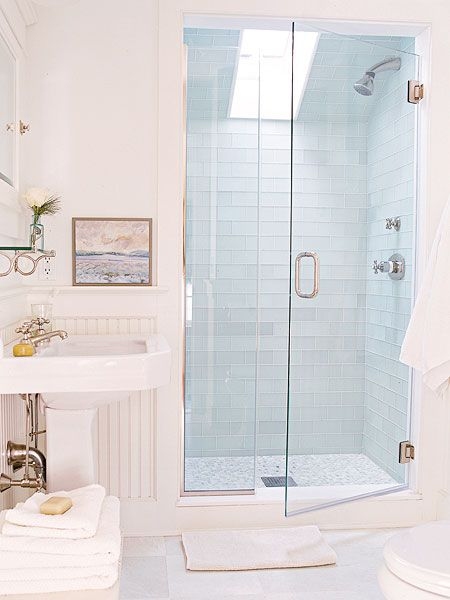 Soft blue glass subway tile and skylight in the shower create a serene bathroom escape.