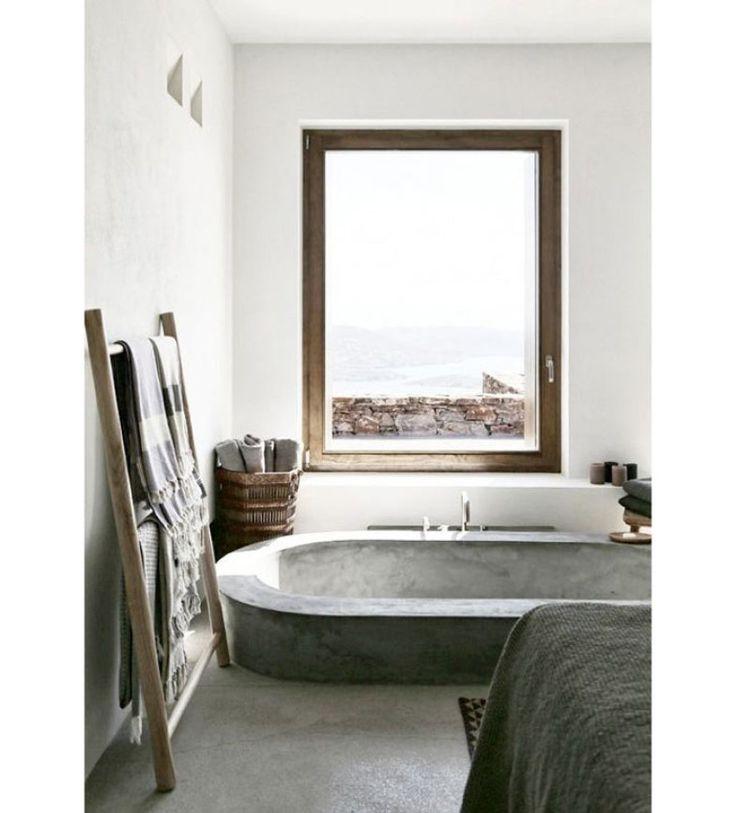 Em frente à uma janela de moldura de madeira, paredes brancas e banheira de cimento queimado completam este ambiente