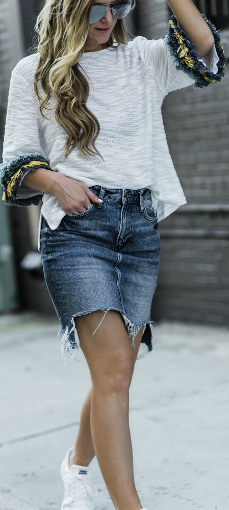 Sporty chic outfit styled with fringe sleeve top, distressed denim skirt, and adidas sneakers