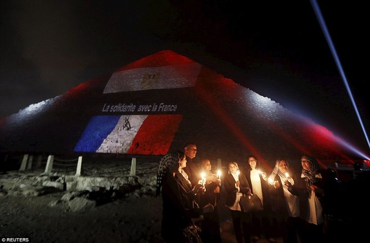 Egyptians light candles as the French and Egyptian flags are projected on to one of the pyramids of Giza in Egypt