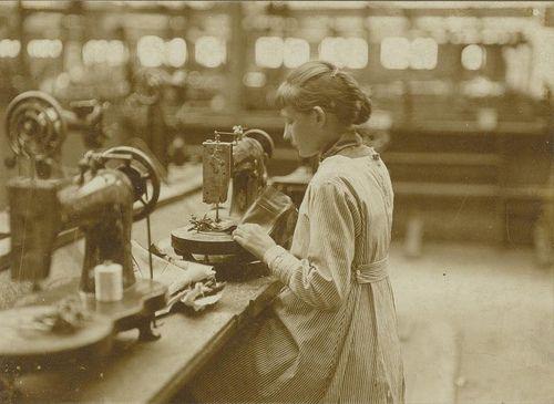 Knoopsgatenmachine bediend door een meisje van 15 jaar; dat is veel eenvoudiger werk dan het stikken, men leert het in enkele weken. Schoenfabriek Jan van Arendonk, Tilburg, Nederland, 1928.