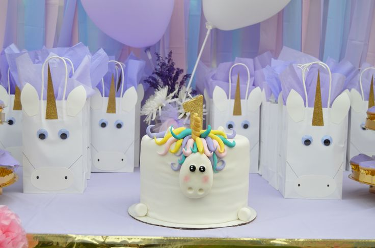 Unicorn birthday party/ White bags are from target. Tissue paper from the dollar tree (it came in a pack of pastel colored sheets). Unicorn hand drawn and cut out on a gold glittery thick paper purchased from JoAnn Fabric. Unicorn eyeballs from Hobby Lobby. I made the gold glittery candle with a plain yellow candle. Covers it in school glue than sprinkled gold glitter all over it. I used Martha Stewart fine gold glitter.