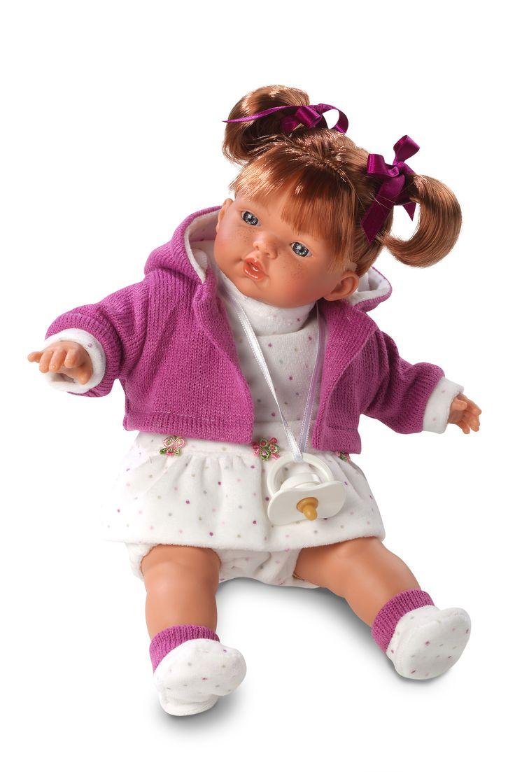En fantastiskt söt taldocka, klämmer man på magen kan dockan säga mamma, pappa och gråta.  Dockan har rödblont hår uppsatt i två höga tofsar samt en lila jacka