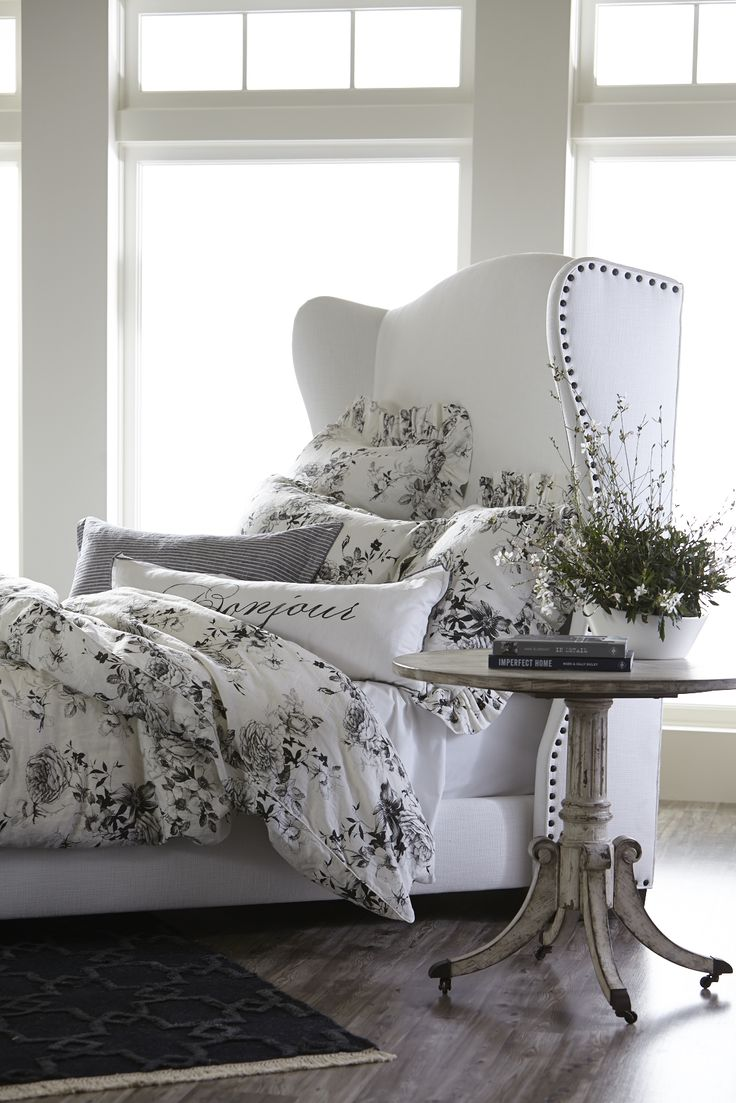 crisp neutral white bedroom with delicate black accents black and white toile bedding white nailhead bed weathered hardwood floors