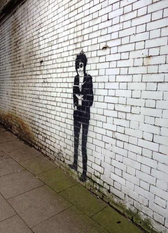 John Cooper Clarke as seen under a bridge in Salford, Greater Manchester, England, United Kingdom, 2014, photograph by Katy Block.