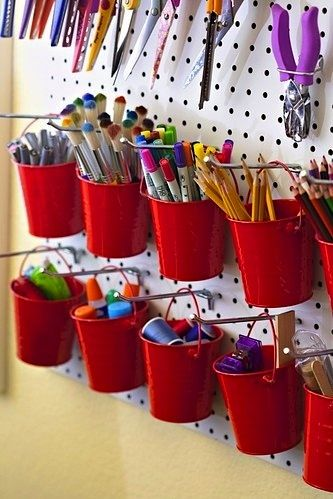 red bucket containers hanging from pegboard for activity room storage. This would be much easier for the girls to take their supplies on and off the board as needed.  Dollar store????