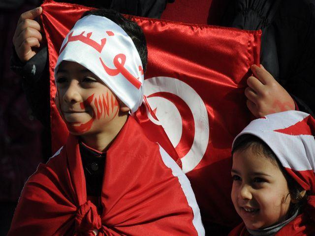 2 enfants portant le drapeau de la Tunisie