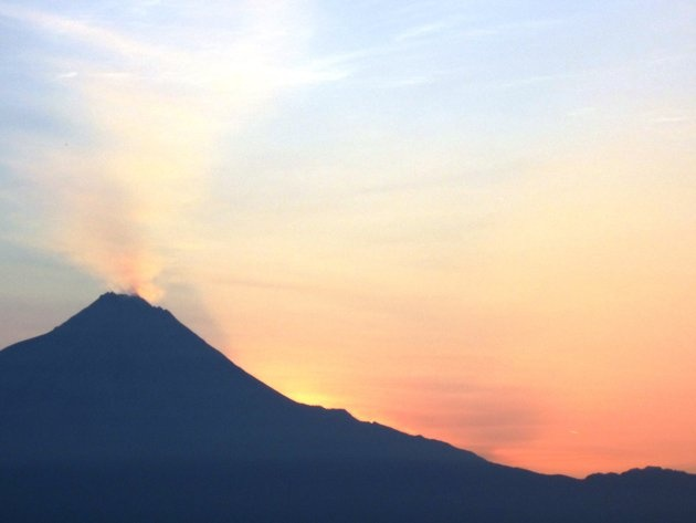 The sun rises from behind Merapi