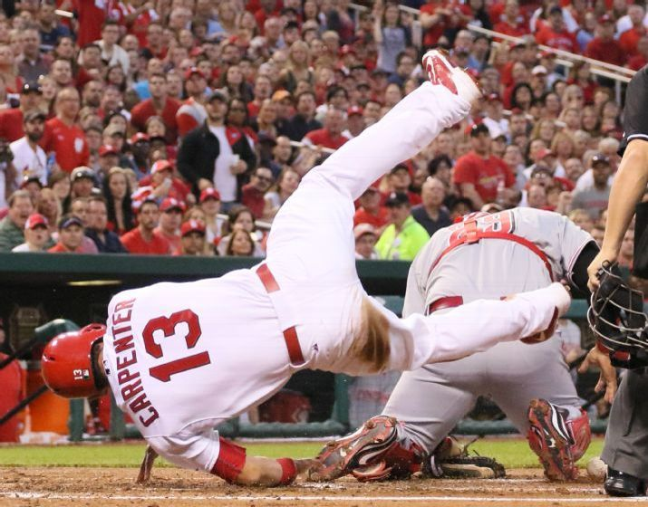 Matt Carpenter goes over Cincinnati Reds catcher Brayan Pena to score during the first inning of the game. Cards won 6-1.  4-17-15