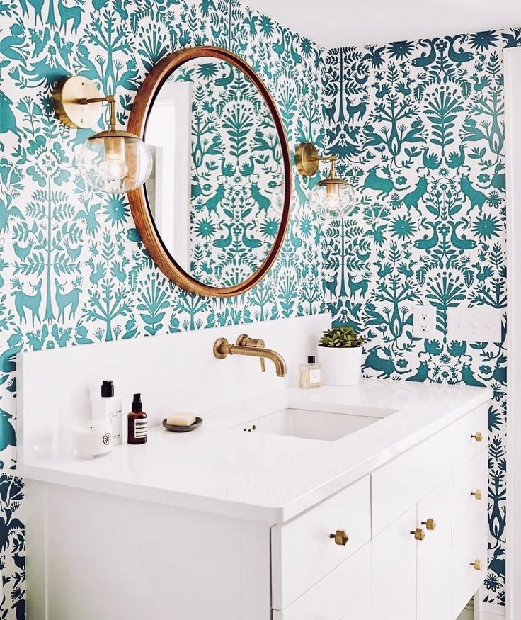 Teal otomi wallpaper in white and gold modern bathroom