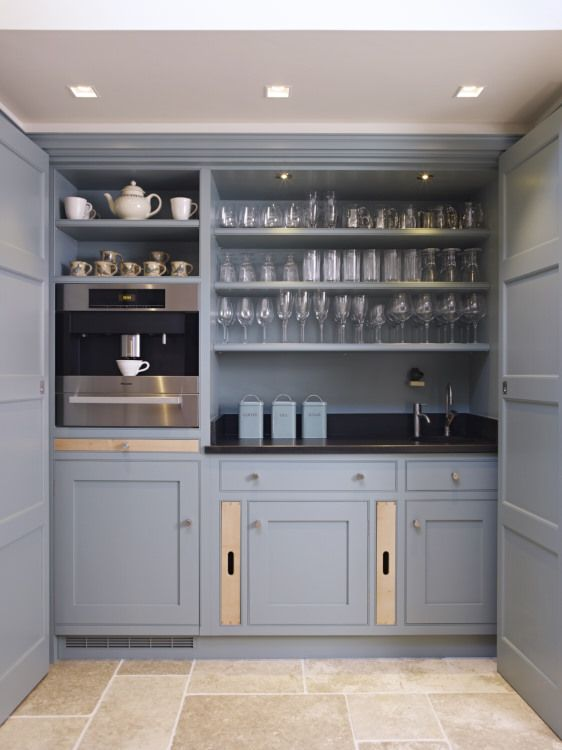 This bespoke drinks bar hideaway, featuring a Miele coffee machine, contrasts beautifully with the black worktop and stone floors #kitchendesign