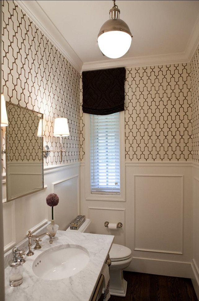 A Moroccan inspired grasscloth from Phillip Jeffries and white wainscoting give a fresh look to the powder room.