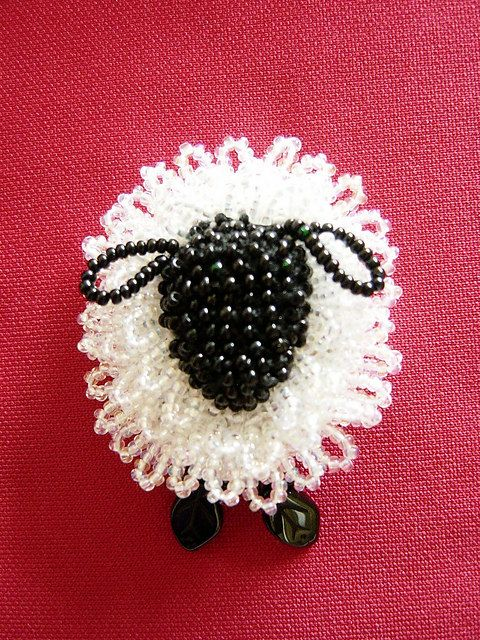 A bead-knitted sheep pin looks good on a lapel or even a felted hat!    Made with black and white perle cotton, crystal and black seed beeds, with