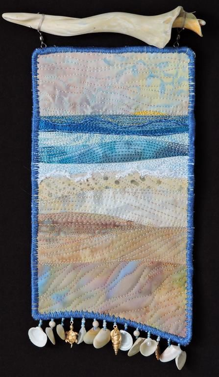 Everyday at the Beach is Different #3. Small fiber art quilt by Eileen Williams. It is hanging from found a shell fragment.