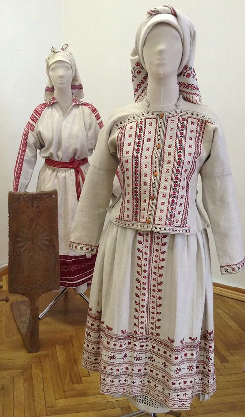 """Women's festive costumes. The end of the 19th century – the early beginning of the 20th century. The one at the left is from Volyn region. It consists of a shirt, an apron, an apron-like garment called """"prytulka"""", a belt called """"krayka"""", a kerchief. The one at the right is from Lviv region of Ukraine, Yavoriv district. It consists of a shirt, a skirt-haze, an apron called """"zapaska"""", a jacket called """"kabat"""", and a kerchief"""