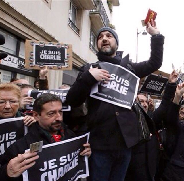 Journalist hold up their press cards outside the offices of Charlie Hebdo during a minute of silence.